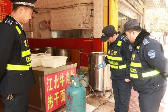 执法队员在对一家早餐店门前的瓶装气进行燃气检测